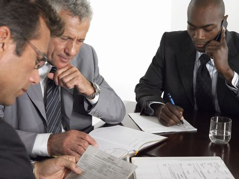 Multiethnic businessmen with paperwork at conference table