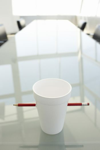 Disposable cup pierced by pencil on table in conference room