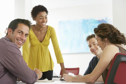 Portrait of young businessman with colleagues in meeting room