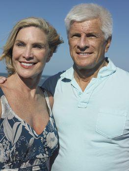 Happy senior couple with arm around on beach vacation