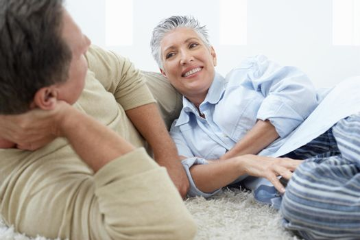 Relaxed couple lying on rug at home