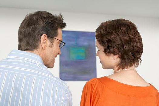 Rear view of couple discussing painting in art gallery