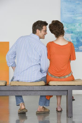 Rear view of couple looking at painting in art gallery