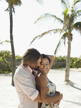 Couple embracing on beach half length
