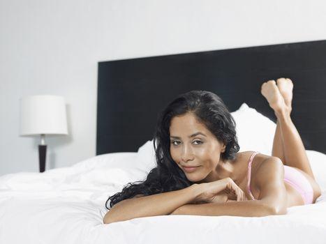 Woman in underwear reclining on bed