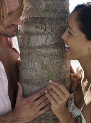 Closeup of a romantic couple standing by a tree trunk
