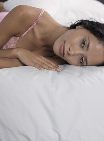 Mid-adult woman lying down on bed head and shoulders