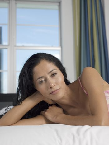 Portrait of mid-adult woman lying down on bed head and shoulders