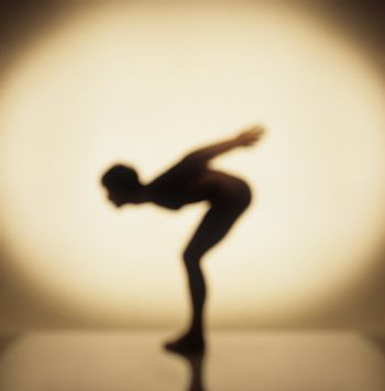 Silhouette of a man performing aerobics in front of the spotlight