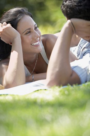 Couple talking face to face lying on park lawn