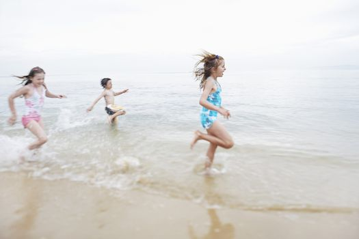 Excited young children running in surf at beach