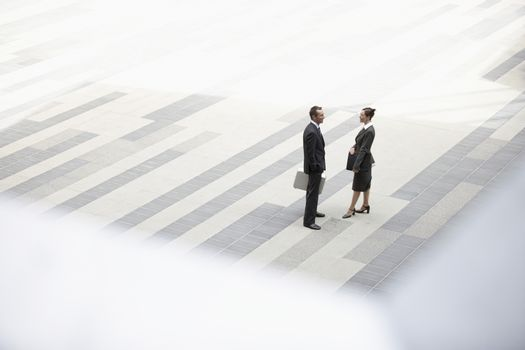 High angle view of businessman and businesswoman standing in outdoor plaza