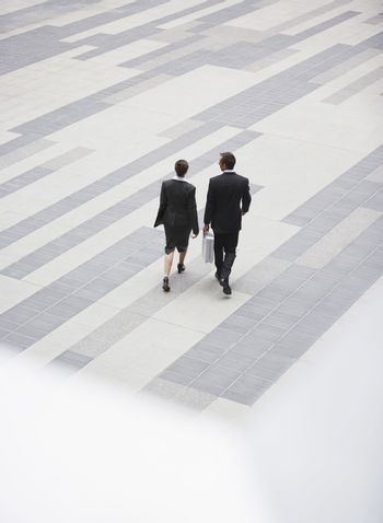 High angle rear view of businesspeople walking in outdoor plaza