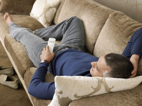 Man laying on sofa watching TV