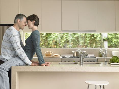 Happy couple rubbing noses at kitchen counter