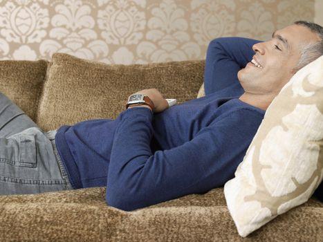 Smiling man laying on sofa