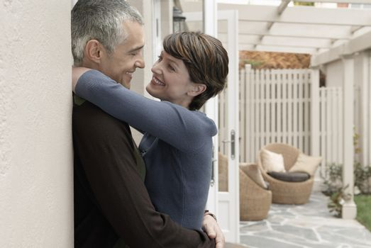 Side view of happy loving couple embracing at porch