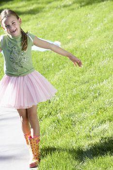 Portrait of cute girl walking on sidewalk at garden
