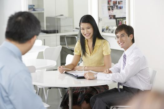 Young Asian business people having discussion in meeting room
