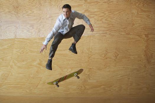 Full length of a businessman on skateboard in midair