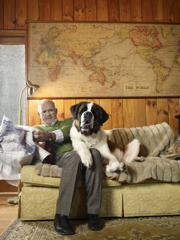 Senior man reading newspaper while sharing sofa with large St Bernard dog