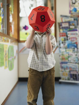 Small boy hiding his face with a numerical ball