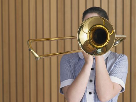 Young teenager practicing with trombone