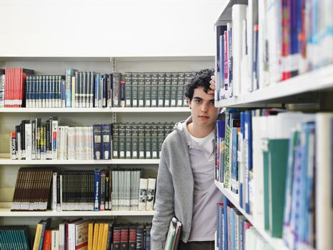 Portrait of a young male standing by the book shelf