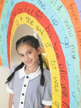 Portrait of elementary schoolgirl standing under painted arch in classroom