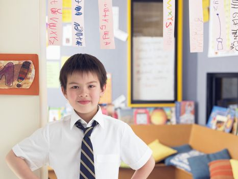 Elementary schoolboy learning to read from hanging paper strip in classroom
