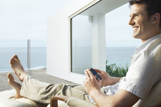 Young man relaxing on porch using mobile phone