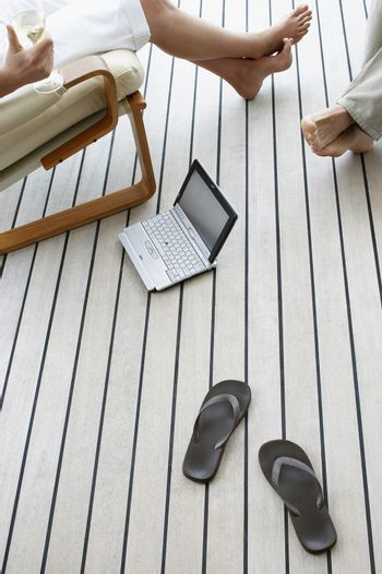 Low section of couple with slippers and laptop on floor