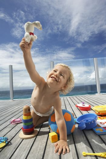 Baby Boy Playing on Porch with lots of toys