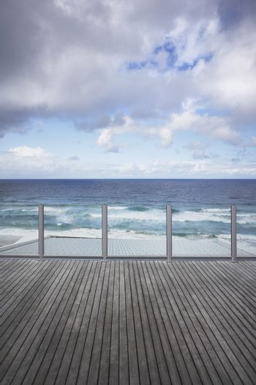 Wooden dock overlooking ocean against cloudy sky