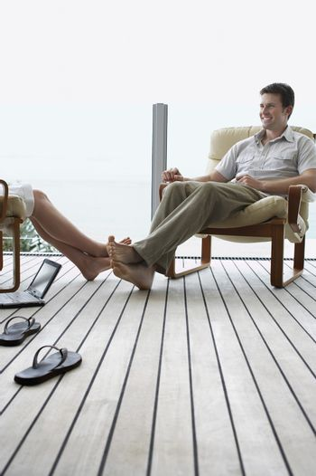 Happy young man with woman relaxing on porch