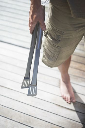 Low section of young boy holding kitchen tongs