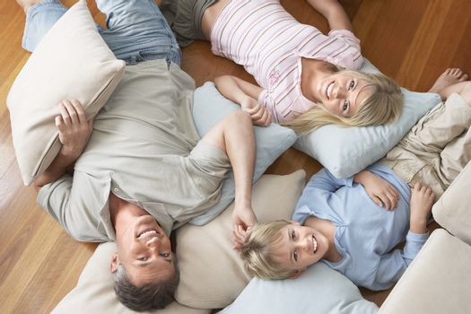 Portrait of happy family of three lying on floor with cushions at home