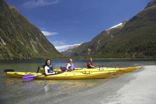 Three people in kayaks at shore of mountain lake