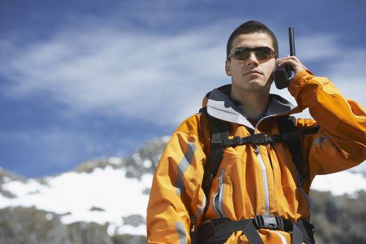 Man using walkie-talkie on mountain peak