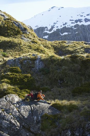 Side view of two hikers sitting on boulders in mountain valley