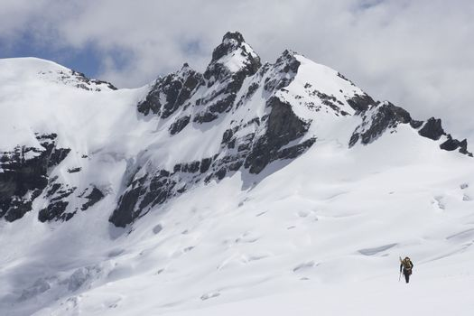 Rear view of a hiker heading towards the distant peak in snow