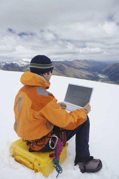 Rear view of a male hiker using laptop on snowy mountain landscape