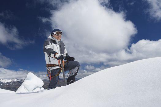 Male mountain climber reaching snowy peak against clouds