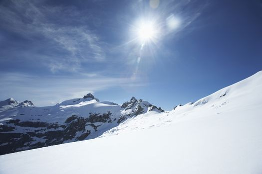 Snow-topped mountain peaks under the sun