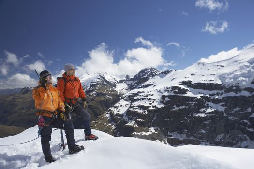 Two male mountain climbers on snowy peak against sky with one using walkie talkie