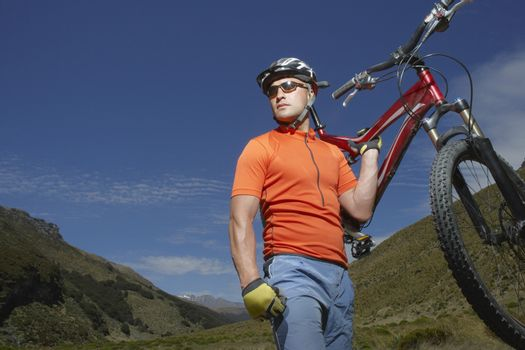 Cyclist carrying bike in countryside