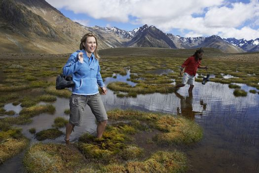 Two hikers wading through pond against mountains