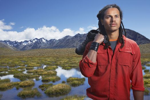 Mixed race man holding shoes by ponds against mountains
