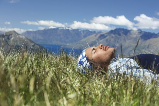 Young mixed race man resting in the field against mountain range