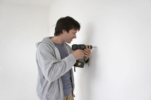 Young man drilling hole in the wall